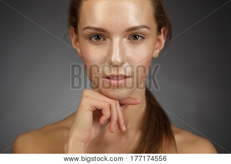 Portrait Of A Thin And Beautiful Girl With A Shiny, Perfect Skin. She Holds A Finger Near Her Chin
