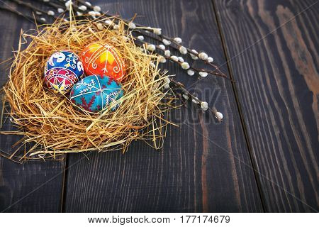 Easter eggs in a nest with willow twigs on a wooden table. The concept of the Easter holidays and folk art.