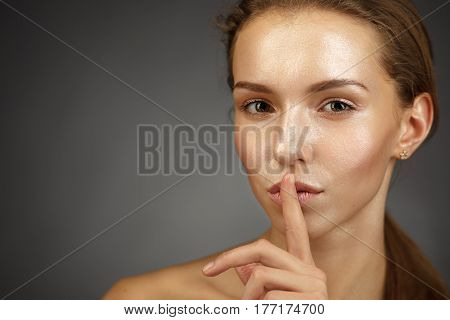 A Beautiful And Young Girl With A Shiny Skin Puts Her Finger To Her Lips. Keep A Secret