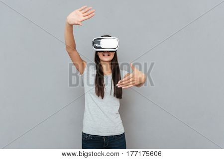 Pleased woman using virtual reality device in studio over gray background