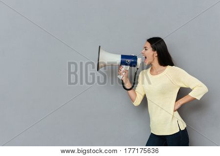 Side view of angry woman in sweater which screaming in megaphone and holding arm at hip over gray background