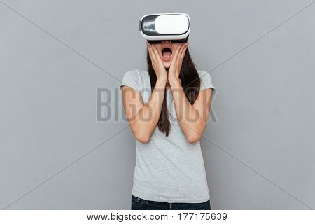 Shocked woman using virtual reality device and holding arms on cheeks over gray background