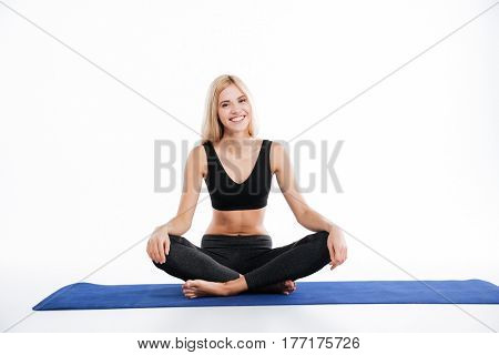 Image of happy fitness woman sitting make yoga exercises and posing isolated over white background. Looking at camera.