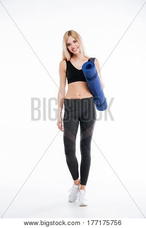 Picture of cheerful fitness lady standing and posing isolated over white background. Looking at camera and holding sports rug.