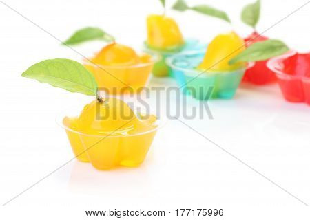 Orange deletable imitation fruits in jelly cup on white floor.