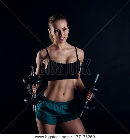 Cute athletic model girl in sportswear with dumbbells in studio against black background. Ideal female sports figure. Fitness woman with perfect sculpted muscular and tight body