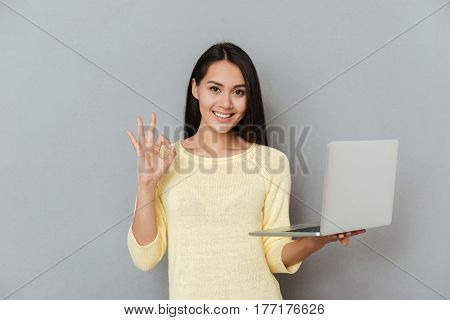 Woman in sweater which holding laptop and showing ok sign while looking at camera isolated gray background