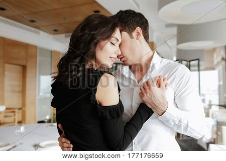Picture of young loving smiling couple dancing in restaurant indoors. Looking aside.