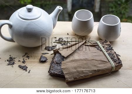One pack of black chinese tea with white teakettle and two cups with green leaves as background