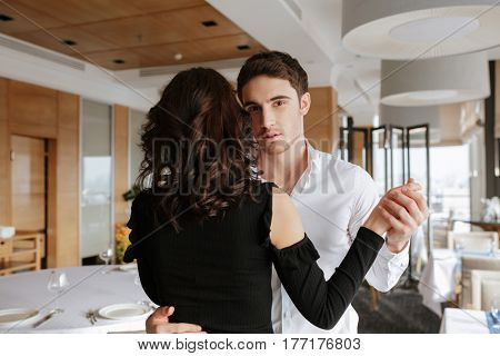 Image of young loving couple dancing in restaurant indoors. Man looking at camera.