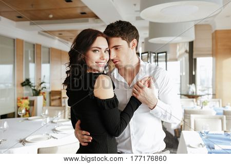 Image of young loving happy couple dancing in restaurant indoors. Woman looking at camera.