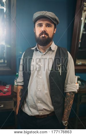 Young man with cigarette looking at camera. Bearded hipster with cocky look and tattoos indoor, free space. Bad habit, criminal, health, safety, addiction concept