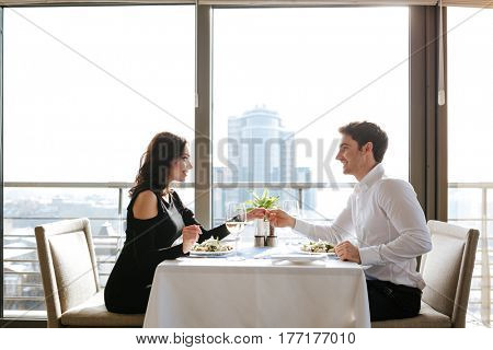 Picture of young happy loving couple sitting in restaurant indoors while talking and eating. Looking at each other.