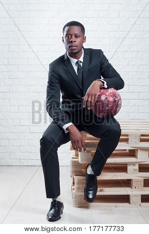 Basketball player with a ball. Sportsman wearing business suit on white brick wall background.
