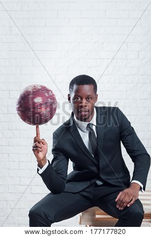 Successful african sportsman with a basketball wearing business suit on white brick wall background.