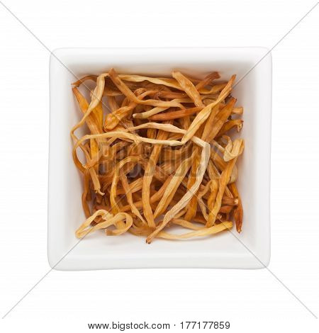 Traditional Chinese Medicine - Jin Zhen (dried daylilies) in a square bowl isolated on white background