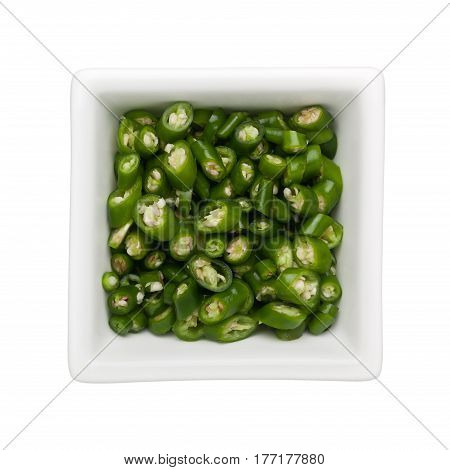 Sliced green chilli in a square bowl isolated on white background