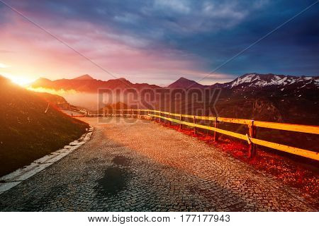 A look at the sunlit hills at twilight. Dramatic and gorgeous morning scene. Location place Grossglockner High Alpine Road, Austria. sightseeing Europe. Outdoor activity. Explore the world's beauty.