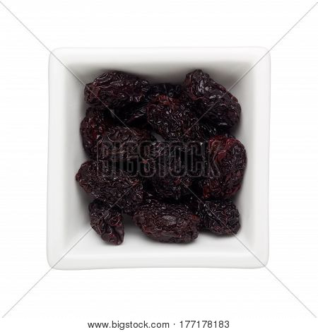 Dried black dates in a square bowl isolated on white background