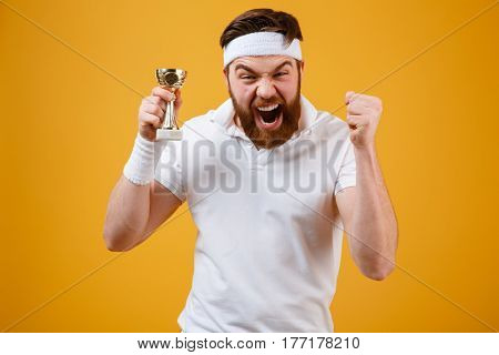 Picture of emotional young sportsman holding reward dressed in white t-shirt standing isolated over yellow background make winner gesture. Looking at camera.