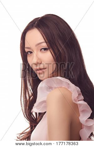 Beautiful young asian woman with long curly hair on white background. Close-up portrait of gorgeous girl in pink dress looking at camera