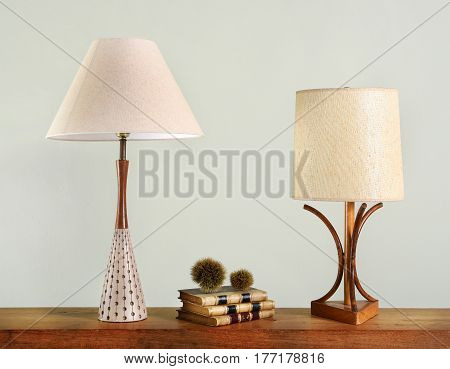 Books On Shelf Between Two Vintage House Lights