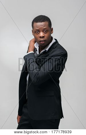 Fashion clothes, brand jackets, expensive men suits. African american guy in office dress code on grey background.