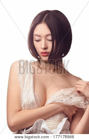 Asian woman dressing or undressing. Gorgeous girl in lacy white wedding dress indoors in studio against white background