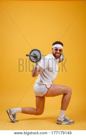 Side view of an excited retro fitness man doing squats with barbell and looking at camera isolated on a orange background