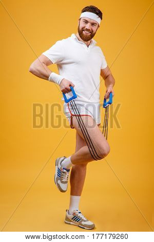 Full length portrait of a sporty man exercising with rubber expander over orange background
