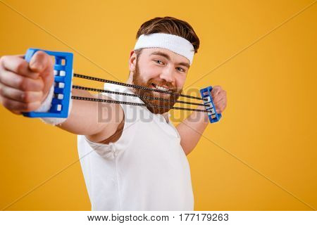 Close up portrait of a young athletic man exercising and doing fitness with a chest expander over orange background