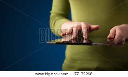 Close up of hand holding digital touchpad tablet device on background