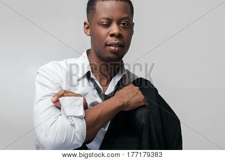 Portrait of african american man on grey background with copy space. Winking, flirting, footsie.
