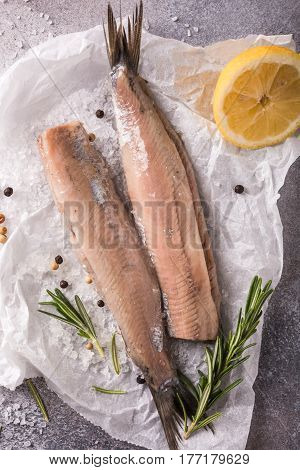 Freshly salted herring with salt, lemon ans rosemary on gray background. Traditional Dutch delicacy. Retro style toned. Top view.