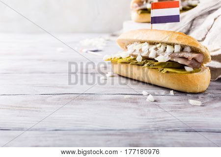 Traditional dutch snack, seafood sandwich with herring, onions and pickled cucumber. Broodje haring. Copy space. With flag of Netherlands.