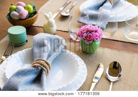 Spring dinner party decoration. Beautiful Easter table settings white decorative bunny, colorful eggs, napkin and cutlery on wooden background with copy space. Happy Easter concept.