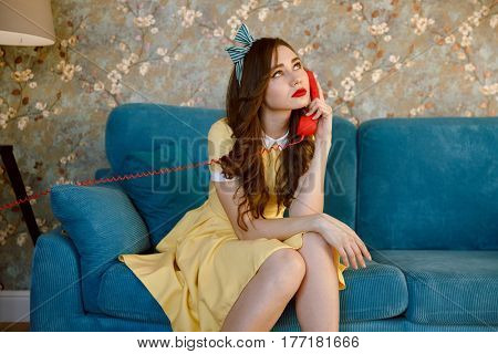 Photo of tired young pin-up lady with red lipstick sitting on sofa at home. Looking aside while talking by phone.