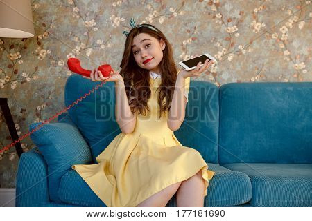 Photo of pretty young pin-up lady with red lipstick sitting on sofa at home. Looking at camera while choose between stationary phone and mobile phone.