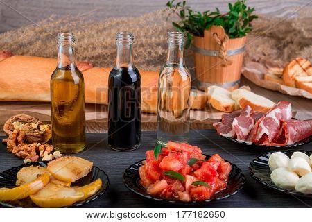 Ingredients On Plates For Preparation Bruschetta Near Bottle With Sauce. Italian Cuisine Food Antipa