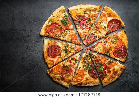 Traditional italian pizza with salami cheese tomatoes greens. Top view at dark stone table. Italian food background.