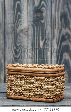 Light brown knitted basket on blue wooden background