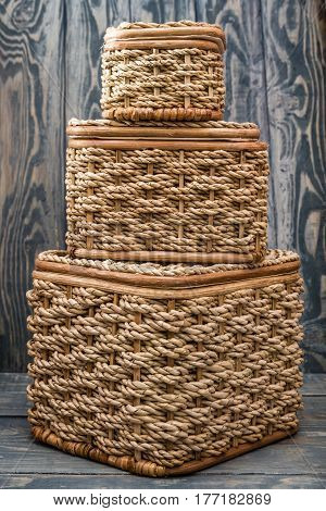 Light brown knitted baskets on blue wooden background