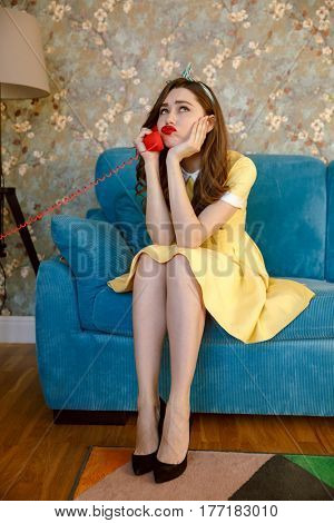 Image of bored young pin-up lady with red lipstick sitting on sofa at home. Looking aside while talking by phone.
