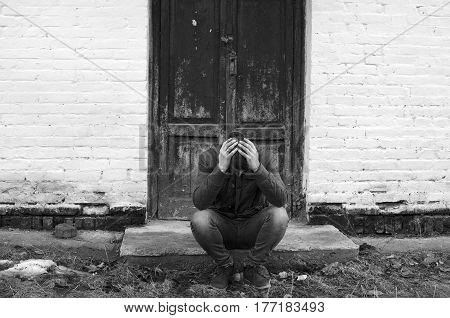 Sad man before the closed door. Black and white photography