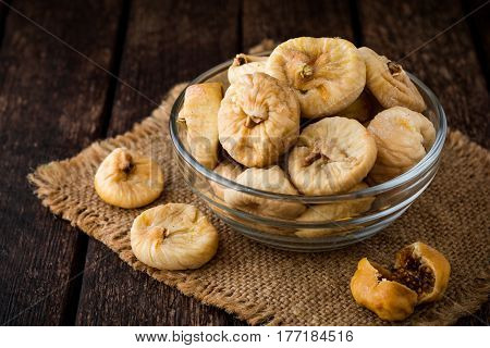 Dried figs in glass bowl on wooden background.