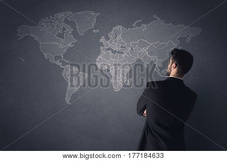 Young businessman in black suit standing in front of a black world map