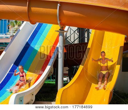 Swimming pool slides for children on water slide at aquapark and thumb up. Summer holiday mood outdoor. Happy childhood of there are two kids girl sisters in aqua park.