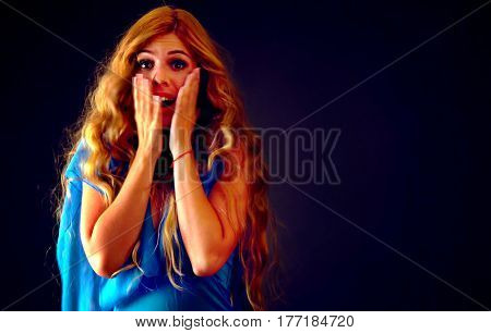 Shocked woman screaming with joyful. Surprised excited happy girl in evening dress shouting with joy or fright and cuddle her hands to her cheeks. Black friday holiday deals. Portrait of women's happy