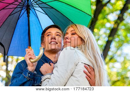 Autumn couple walking park. Fall friends walk under rain umbrella. First date of two young people in rainy day. Blonde girl gently cuddle up to brunette man.