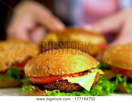 Hamburger fast food with ham on wooden board . Burger with fresh vegetables and cheese slice on blurred background. Piece of cheese hanging from sandwich In blur. Female hand reaches for cheeseburger